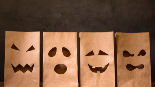 paper bags with scary face on wooden table, halloween concept