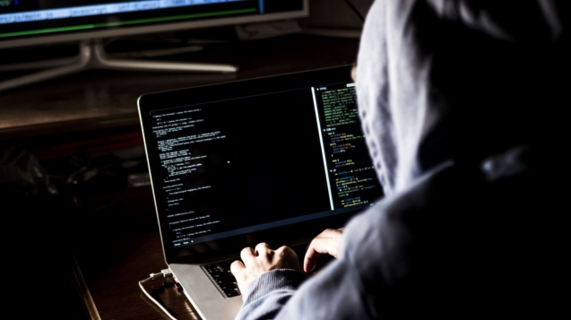 hacker in hoodie typing code in program using laptop in dark studio