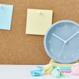Concept of notes, goals, memo or action plan. Sticky notes on cork board and alarm clock  in workplace office or home